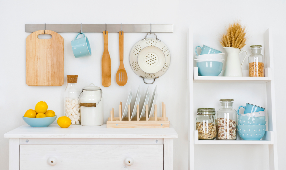 Colorful kitchen tools on a small counter, shelving, and wall rack.