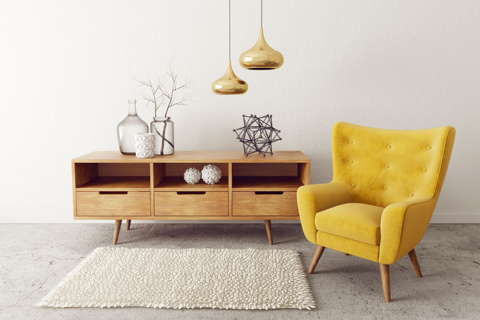 Minimal home decor with yellow armchair next to a square rug, pendant lights, and low wooden cabinet of art objects.